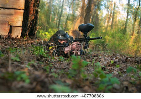 a man in a protective mask plays in paintball, lying on the grass in ambush - stock photo