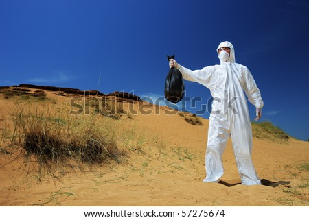 A man in a protective suit holding a waste bag