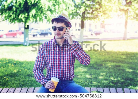 A man in a shirt and jeans and glasses, talking on the phone, a smartphone, the concept of summer, a businessman on vacation. City lifestyle. On the street in the park.
