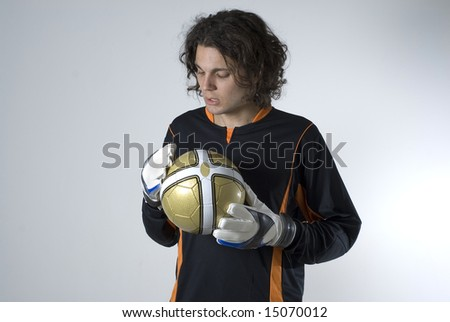 A man in a soccer goalie uniform is posing with a soccer ball.  He is looking down at the ball.  Horizontally framed shot. - stock photo