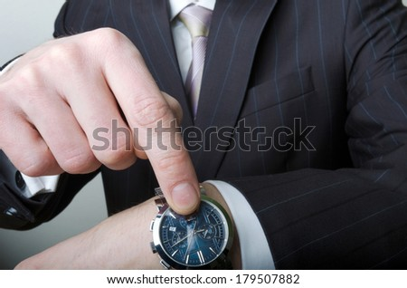A man in a suit, a white shirt and a tie pointing at his watch - stock photo