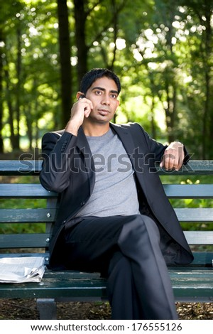 A man in a suit sitting on a bench holding a phone.