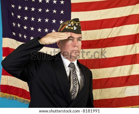 A man in a VFW cap saluting and standing in front of an old faded 48 star American flag. - stock photo