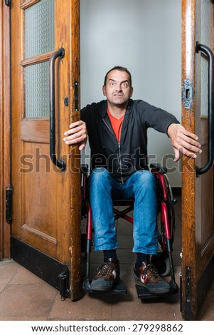 A man in a wheelchair is stuck between swing doors, looking as if in panic and dismay - stock photo