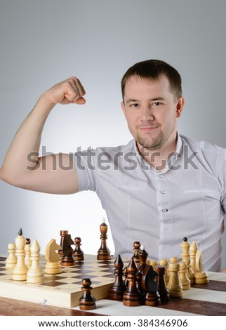 A man in a white shirt shows the power in the game of chess - stock photo