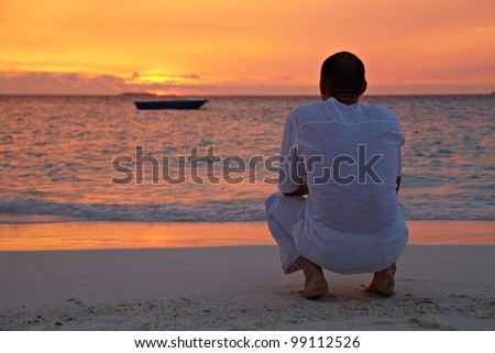 A man in a white shirt sitting on the background of a beautiful sunset in the sea - stock photo