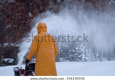 A man in a yellow snow coat uses his red snowblower to clear his sidewalk of snow.  - stock photo
