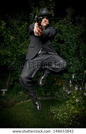 A man in an old style suit, hat and sunglasses jumps while pointing a gun. - stock photo