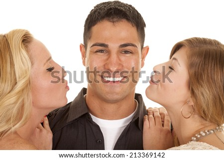 A man in between two women, one of the women with an unhappy expression. - stock photo