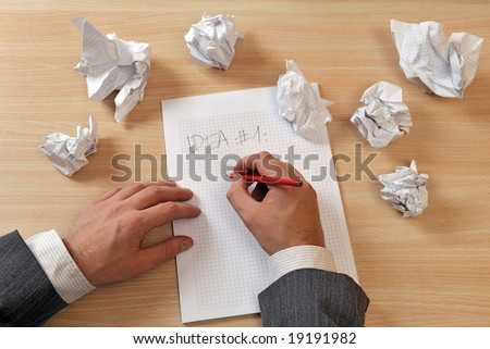 A man in business suite is writing ideas on a paper, with few papers crumpled and discarded