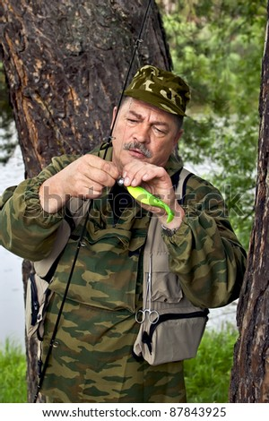 A man in camouflage clothing with spinning and bright green spoon against the trunk of a tree, river, green grass and leaves - stock photo