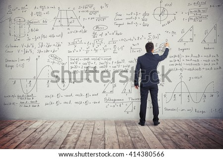 A man in dark business suit is drawing algebraic graphics geometry figures on the white wall and writing down formulas to solve these different mathematical tasks - stock photo