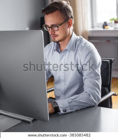 A man in eyeglasses in a shirt working on computer. - stock photo