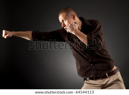 a man in fight action , wearing a shirt over dark background - stock photo