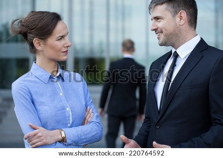 A man in formal clothing talking with his coworker