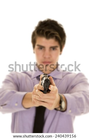 A man in his business clothing holding on to a pistol with a serious expression on his face.