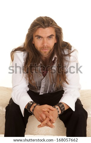 a man in his formal attire sitting on a bench with a small smile on his lips - stock photo