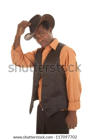 a man in his orange shirt and black vest putting on his cowboy hat.