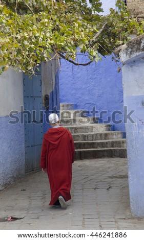 A man in jellaba walks through medina, Chefchaouen, Morocco - stock photo