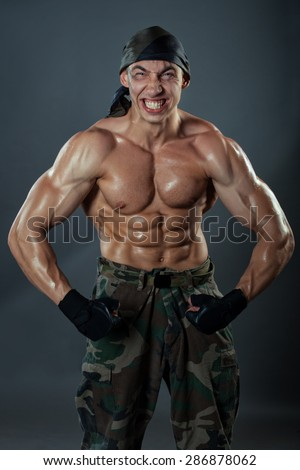A man in military trousers shows his huge muscles. It is strongly strained muscles and face twisted grimace. - stock photo