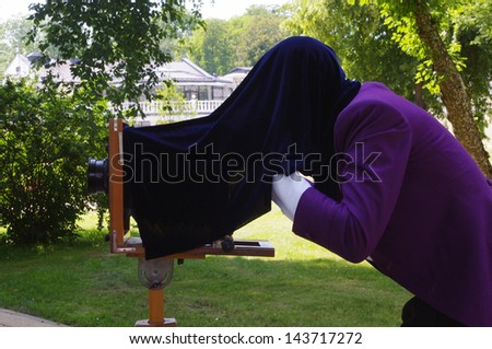 a man in purple tailcoat taking picture with an old wooden camera on a tripod - stock photo