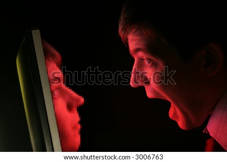A man in shirt and tie screams at a red computer monitor as his own pixelated face emerges from it (coarse pixels) - stock photo