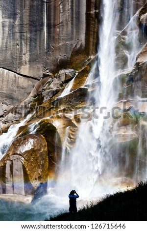 A man in silouette with a binocular is watching the Vernal Falls, in Yosemite National Park. - stock photo