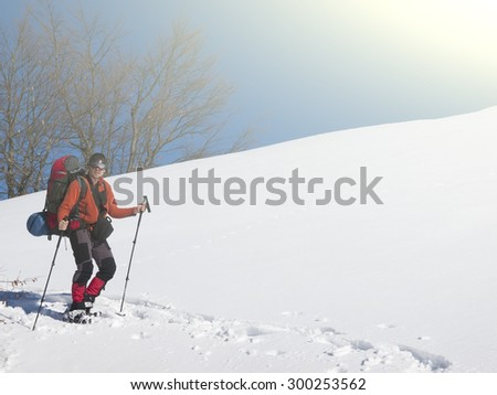 A man in snowshoes and a backpack is in the mountains in the snow.