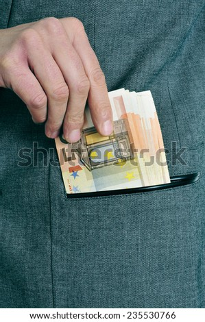 a man in suit getting euro bills in the pocket of his jacket - stock photo