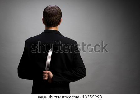 A man in suit holding knife behind back (light gray background version) - stock photo