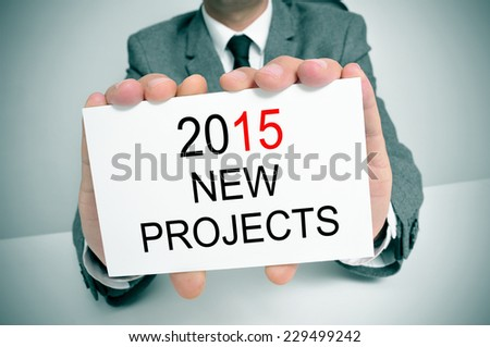 a man in suit in an office desk showing a signboard with the text 2015 new projects written in it - stock photo
