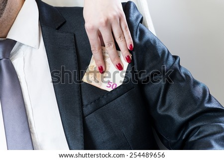 A man in suit talking at smart phone and getting euro bills in the pocket. Corruption. - stock photo