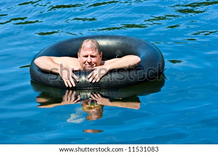 A man in water floating on an inner tube - stock photo
