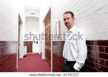 A man in white shirt leans against the wall in a brick and tiled corridor. - stock photo