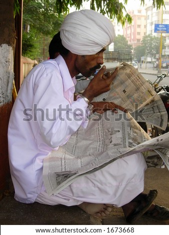 a man in white sipping tea outside a tea stall in indian village
