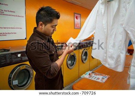 A man inspecting a stain on his clothes at a local laundromat.