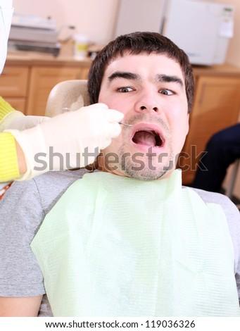 A man is afraid to treat teeth - stock photo