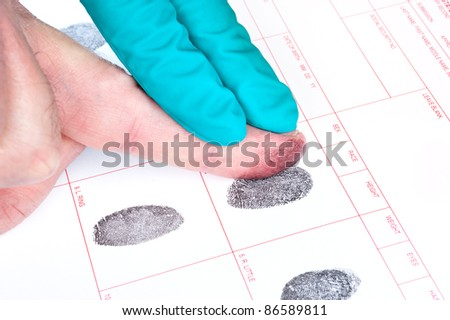 A man is being finger printed for either a crime of for FBI screening on a legal document form. - stock photo