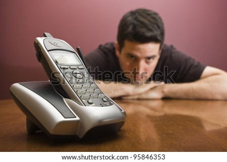 A man is bored waiting for the phone to ring