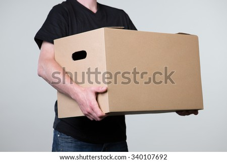 A man is carrying a big cardboard in his hands isolated on a grey background. - stock photo