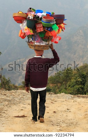 A man is carrying colorful workload on his head and walking on a muddy trail - stock photo
