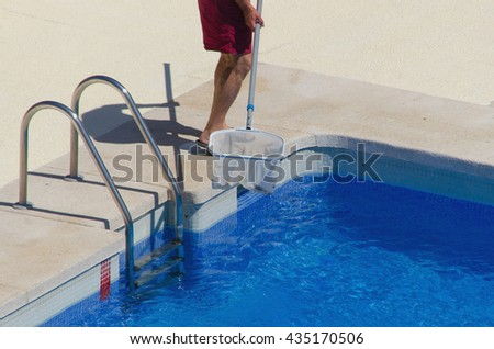 A man is cleaning the swimming pool with a net. Summertime job