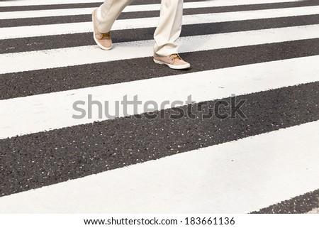 A Man is Crossing a Street by Crosswalk - stock photo
