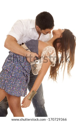 A man is dipping a woman in a blue dress with a white cardigan. - stock photo