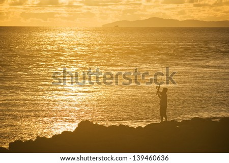 A man is fishing in evening and gold sunset background - stock photo