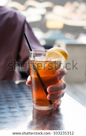 A Man is holding a glass of iced tea. - stock photo