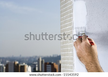 A man is holding a paintbrush and painting a wall white.  Horizontally framed shot. - stock photo