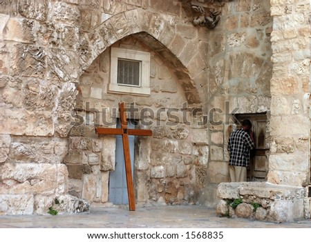 A man is holding his head against the old Etihopian church and praying (Jerusalem, Israel). - stock photo