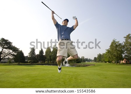 A man is jumping up and down on a golf course.  He is holding a golf club, smiling, and looking away from the camera.  Horizontally framed shot. - stock photo