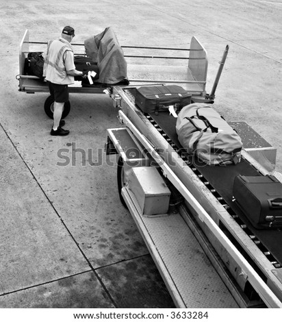 A man is loading luggage onto airplane - black and white version. - stock photo